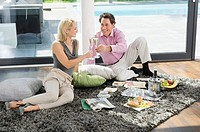 Happy couple having champagne breakfast on rug
