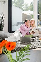 Couple on rug with magazine and laptop
