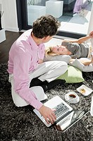Couple with laptop and cup of coffee on rug
