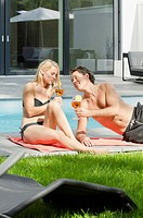 Couple drinking cocktails by the poolside