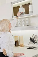 Senior woman taking coffee maker from kitchen cupboard