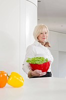 Senior woman holding bowl of lettuce in kitchen
