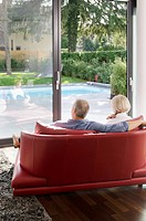 Senior couple on couch looking out to swimming pool