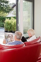 Senior couple on couch reading newspaper