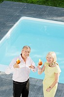 Senior couple with cocktails by the poolside