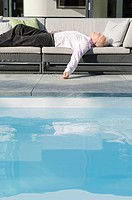 Senior man sleeping by the poolside