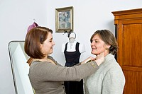 Tailoress adjusting collar of client in studio