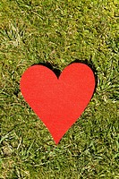 Red heart lying in grass