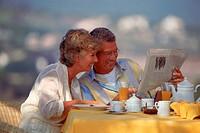 Senior couple having breakfast outdoors