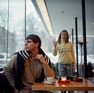 Young Man Waiting in Cafe for Date While Woman Looks In