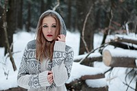 Attractive young woman standing in winter landscape