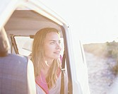 Young Woman Sitting in Car Watching Sunset