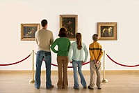 Family Looking at Paintings in Art Gallery