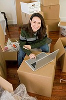Smiling Woman in Middle of Moving Boxes Using Laptop