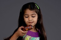 Girl eating a chocolate doughnut