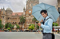 Businessman with an umbrella reading an sms