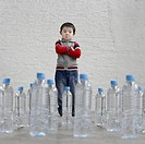 Little Boy Standing with Water Bottles