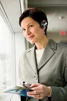 Smiling Businesswoman with Wireless Headset Looking Out Window