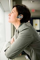 Businesswoman Wearing Wireless Headset Looking Out Window