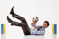 Portrait of smiling businessman playing in goal between files