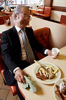 Businessman Eating Fried Food in a Cafe