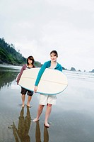 Teenage Girls Carrying Surfboard