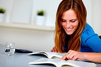 Pretty blonde student woman smiling and reading