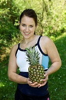Young woman wearing sportswear holding a pineapple