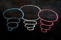 Blank speech bubbles drawn in chalk on a blackboard