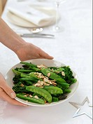 A woman serving a plate of vegetables with slivered almonds Christmas