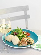 Chicken thighs with pine nuts, bread and salad