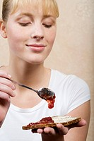 Young Woman Eating Jam on Toast