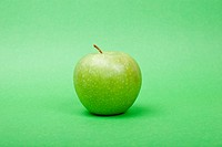 Ripe green apple on green background