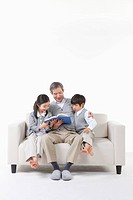 A grandfather and grandsons reading a book