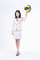 A woman holding up the basketball