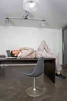 Young Businessman Lying on Desk