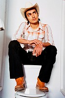 Man in Cowboy Hat Sitting on Top of Toilet