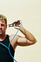 Man Holding Jumper Cable to Head
