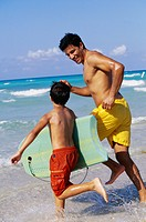 Father and Son Boogie Boarding at Beach
