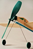 balsawood toy wind-up plane with green propellor and blue rubberband