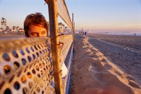 Man by Metal Fence at Beach