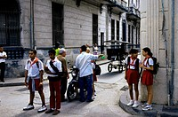 Cuba, Old Havana, Schoolchildren and Local People Standing on Street