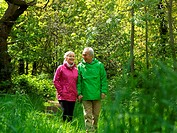 Older couple walking in forest together