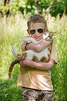Boy carrying cat outdoors