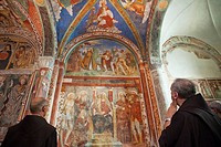 Tourists looking at frescoes depicting the life of Christ, Basilica of San Giulio, San Giulio Island, Lake Orta, Piedmont, Italy