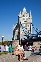 Tourists sitting near a bridge, Tower Bridge, Thames River, London, England