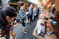 Tourists taking picture of fish at a market stall, Tsukiji Fish Market, Tokyo, Japan
