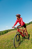 Young woman with mountain bike in spring nature