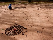 A child creating shapes with chestnut husks