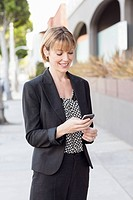 Businesswoman using a mobile phone, smiling